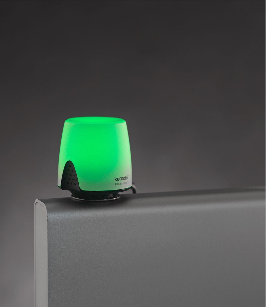 Kuando Busylight Omega viser grøn med en selvklæbende fod på en skærm